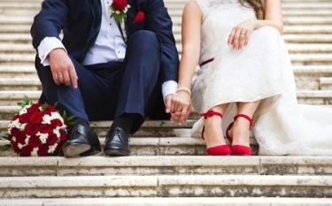 38163405 - unrecognizable young wedding couple holding hands as they enjoy romantic moments outside on the stairs