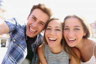 47719268 - group of happy teen friends laughing and taking a selfie in the street
